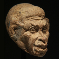 An Egyptian Terracotta Head of a Grotesque
